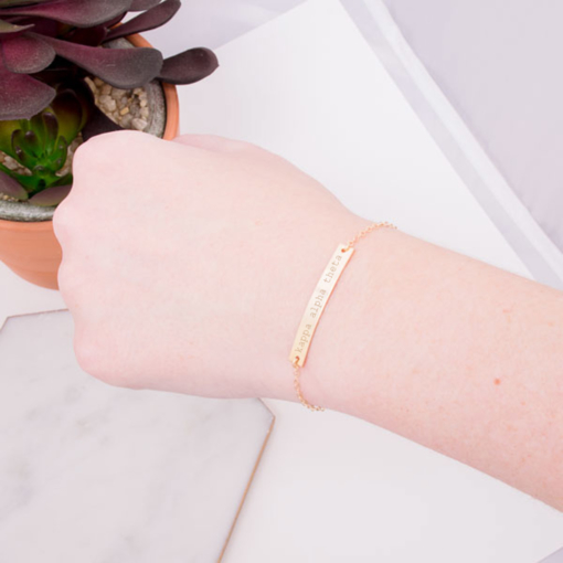 gold-bar-bracelet-on-wrist-engraved